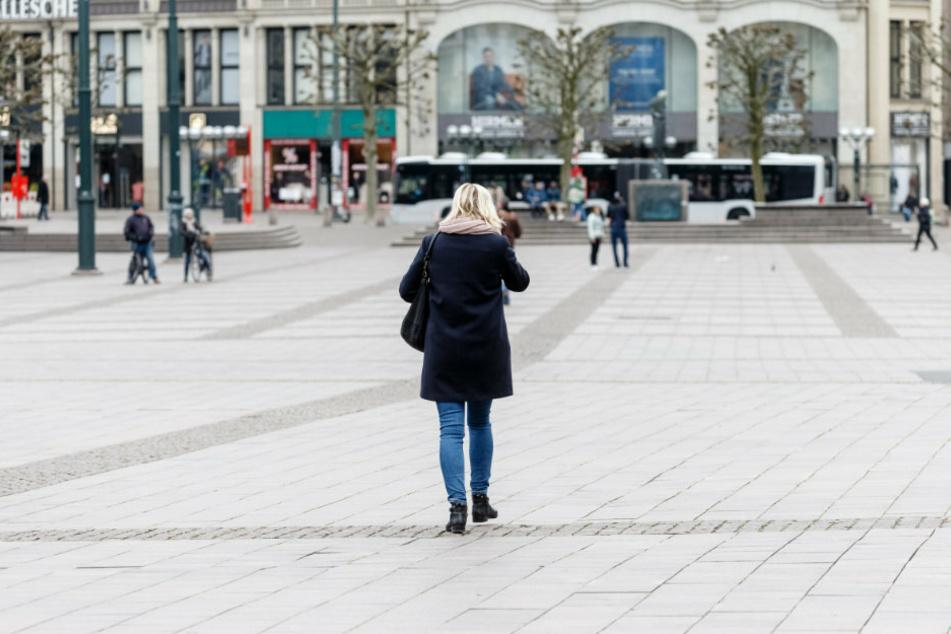 Eine Frau geht gegen 14:30 Uhr über den menschenleeren Rathausmarkt in Hamburgs Innenstadt.
