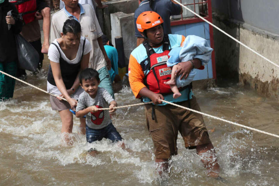 Ein Mitglied der Rettungskräfte trägt ein Baby durch ein überschwemmtes Viertel.