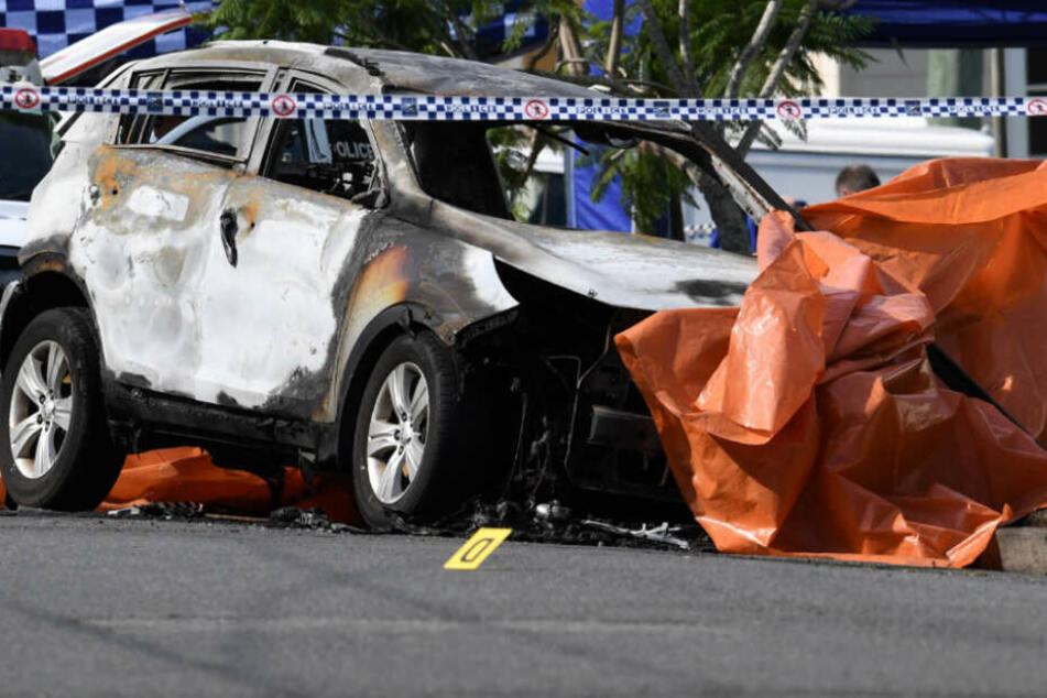 Das Auto der Familie ist völlig ausgebrannt und mit einer orangenen Plane bedeckt.
