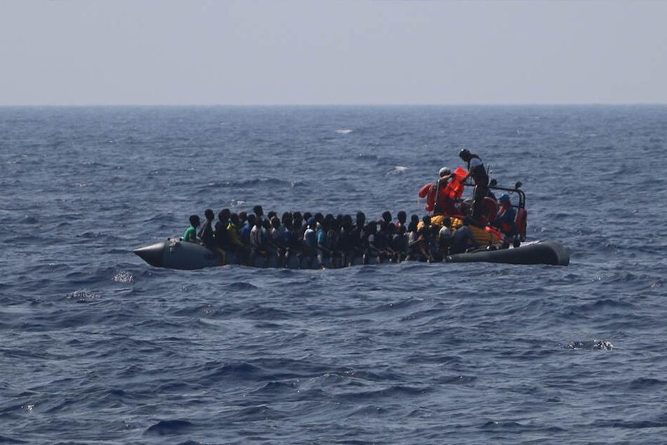 Ein Team der Hilfsorganisation SOS Mediterranee verteilt Rettungswesten auf einem in Not geratenen, im Mittelmeer treibenden Schlauchboot.