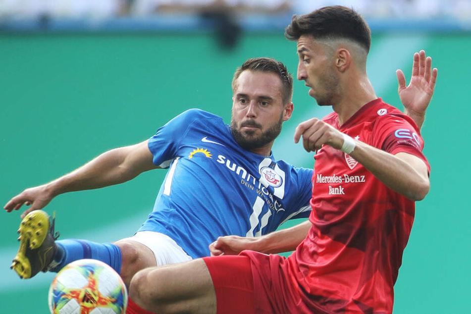 Rostocks Pascal Breier (l) kämpft mit Stuttgarts Atakan Karazor um den Ball.