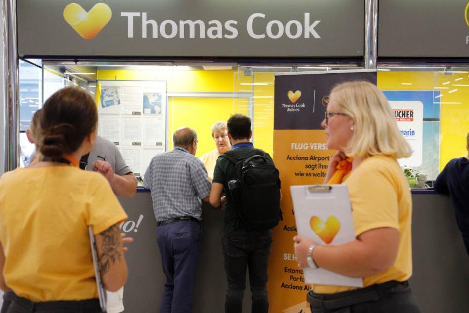 Am Schalter von Thomas Cook stehen Mitarbeiterinnen und kümmern sich um gestrandete Urlauber.