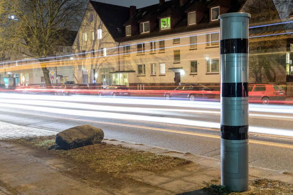 Fahrzeuge fahren an der Osterfeldstraße in Hamburg an einer Blitzersäule vorbei.