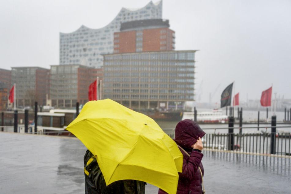 Fußgänger stehen im Regen am Hamburger Hafen.