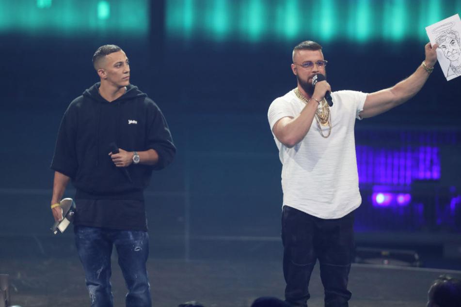 Der Rapper Kollegah hält eine Karrikatur von Sänger Campino mit Heiligenschein hoch.
