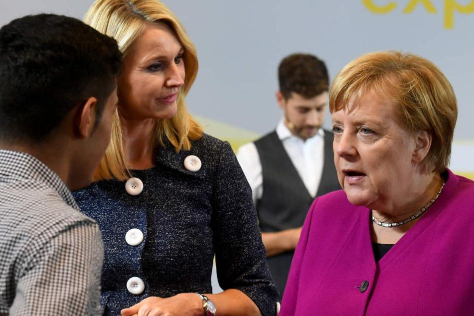 Merkel (r) begrüßt zusammen mit Ariane Reinhart (M), Continental-Personalvorstand, einen jungen Mann in der Zentrale des Continental-Konzerns.