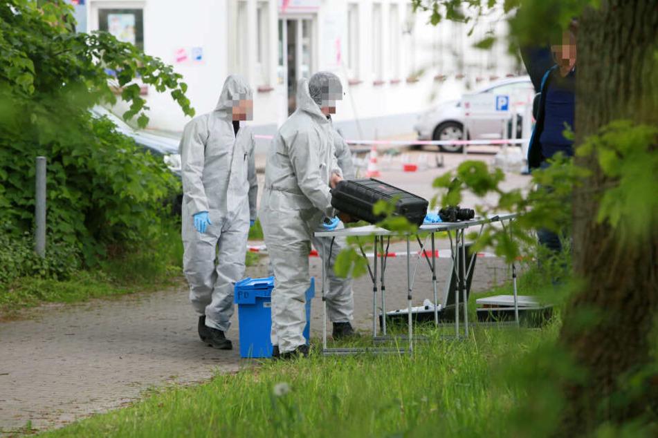 Mitarbeiter der Spurensicherung stehen unweit des Ortes, an dem die Leiche des Tatverdächtigen gefunden wurde.