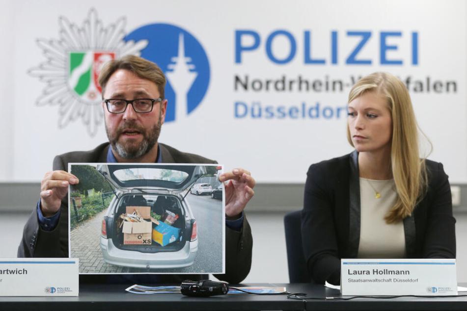 Polizei-Pressesprecher André Hartwich und Staatsanwältin Laura Hollmann zeigen ein Bild des Tatfahrzeugs.