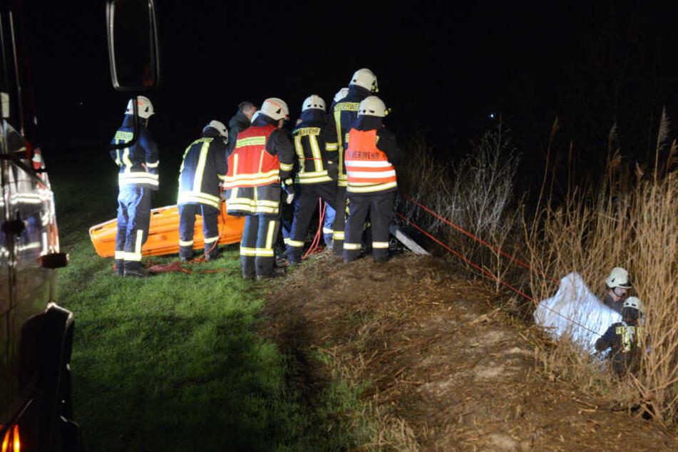 Einsatzkräfte der Polizei und Feuerwehr sind auf einer Wiese bei Groß Kreutz und bergen eine Leiche.
