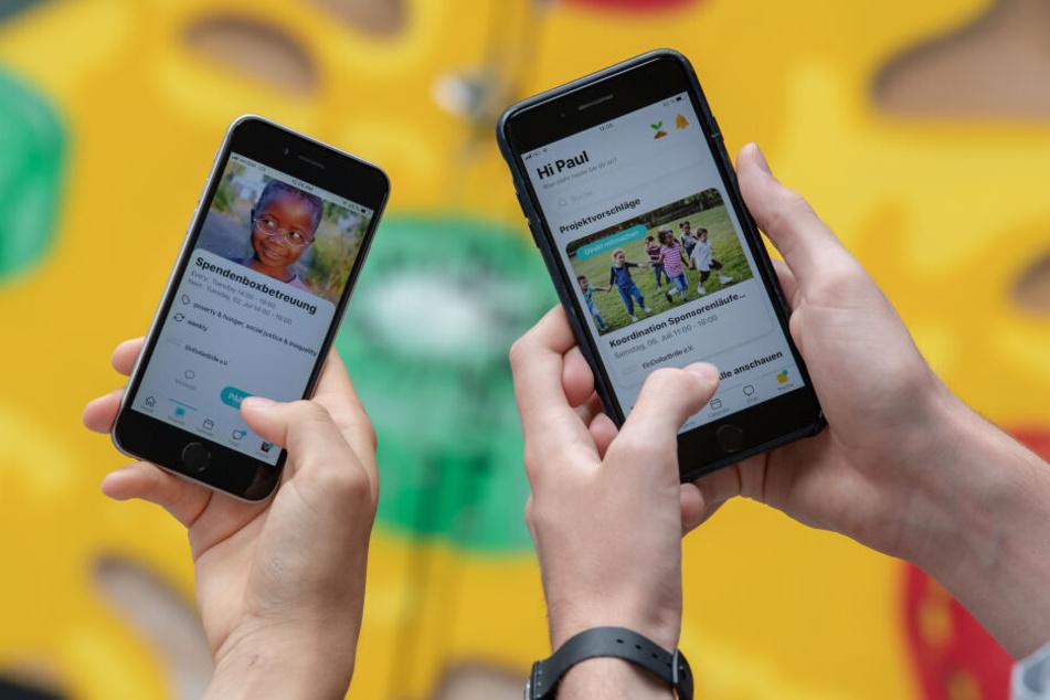 Die beiden App-Entwickler Ludwig Petersen und Paul Bäumler halten zwei Mobiltelefone mit ihrer selber entwickelten App auf dem Display in den Händen.