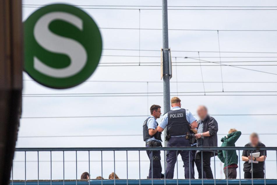 Polizisten und Ermittler in Zivil besprechen sich auf dem Bahnsteig des S-Bahnhofs.
