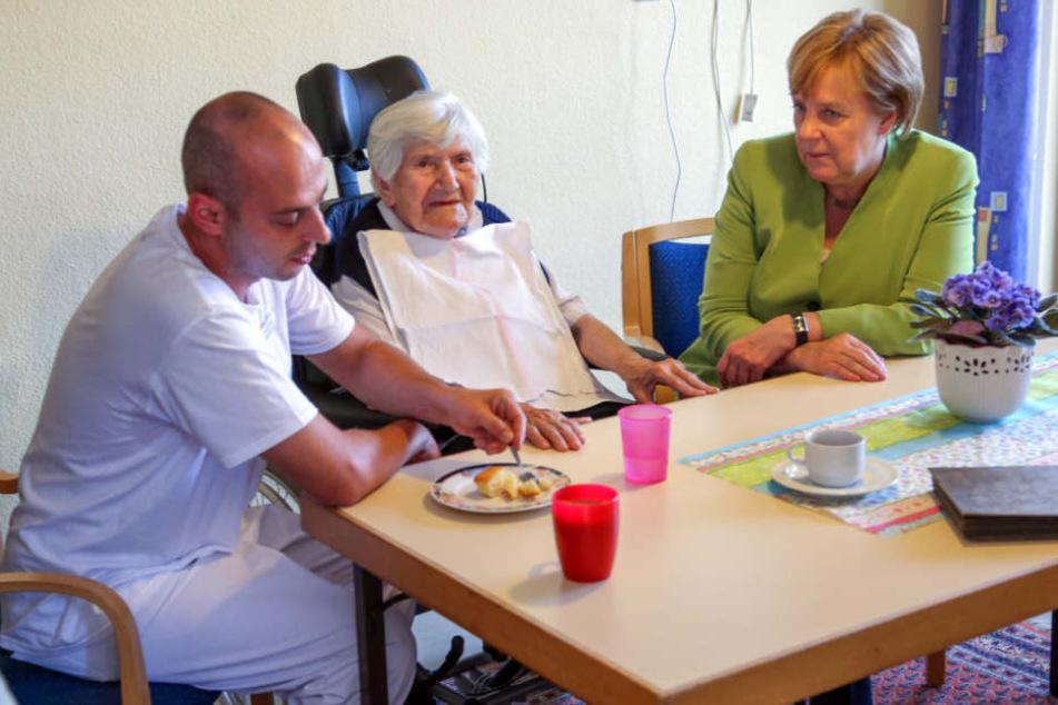 Die Bundeskanzlerin begleitet Ferdi Cebi (links) bei seiner Arbeit.