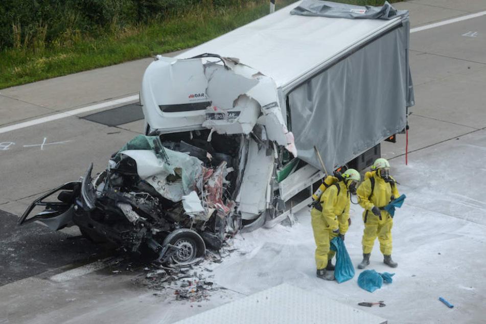 Feuerwehrmänner in Schutzanzügen an der Unfallstelle.