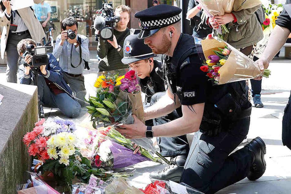 Britische Polizisten legen Blumen für die Opfer nieder.