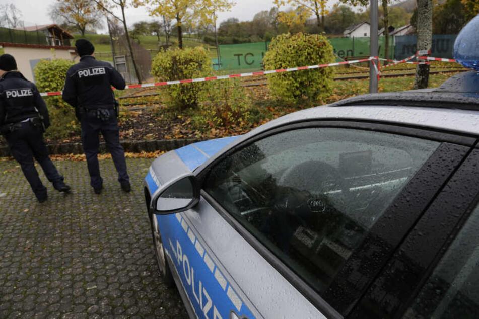 Polizisten stehen vor einem Flatterband.