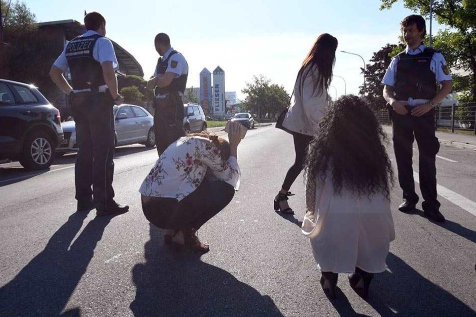 Polizisten und Zeugen stehen vor dem Tatort in Konstanz.