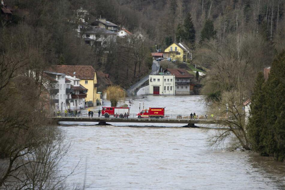 Feuerwehrfahrzeuge stehen auf der Ilzbrücke im Stadtteil Hals: Das Hochwasser hat in Teilen Passaus Straßen und Grundstücke überflutet und Keller volllaufen lassen.