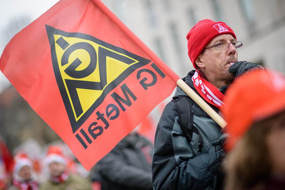 Mit IG Metall-Flaggen ziehen die Demonstranten auf die Straße.
