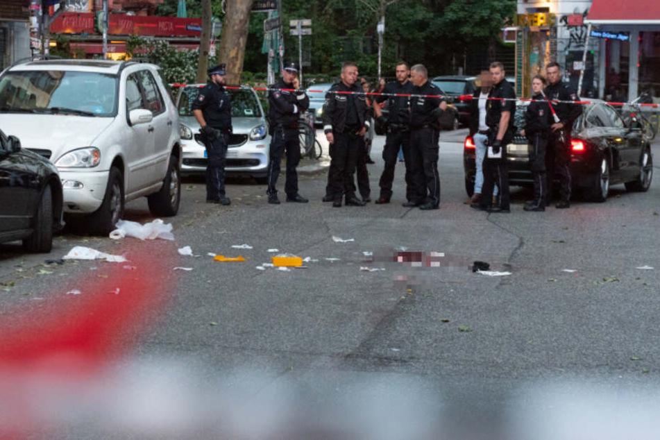 Polizeibeamte stehen vor dem abgesperrten Tatort.
