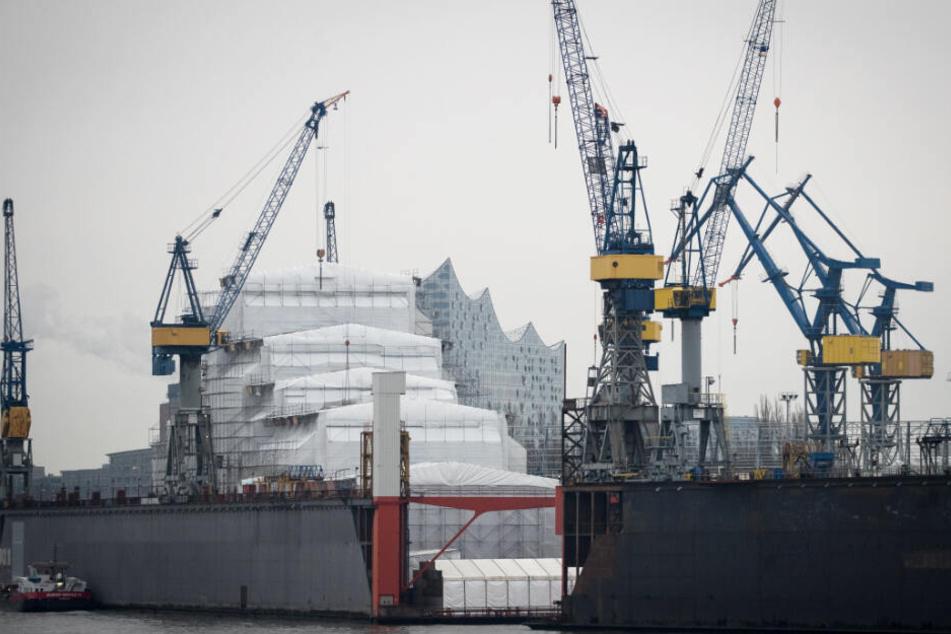Diesen Anblick gibt es bald nicht mehr: Die Silhouette der Elbphilharmonie zeichnet sich hinter einem mit Planen geschützten Schiff im Schwimmdock 10 bei Blohm+Voss ab.