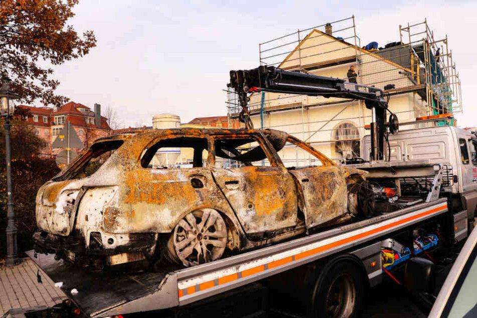 Das Fluchtfahrzeug: Der ausgebrannte Audi wurde gestern aus der Kötzschenbroder Straße abtransportiert. Im Wrack hatten die Ermittler entscheidende Hinweise gefunden.