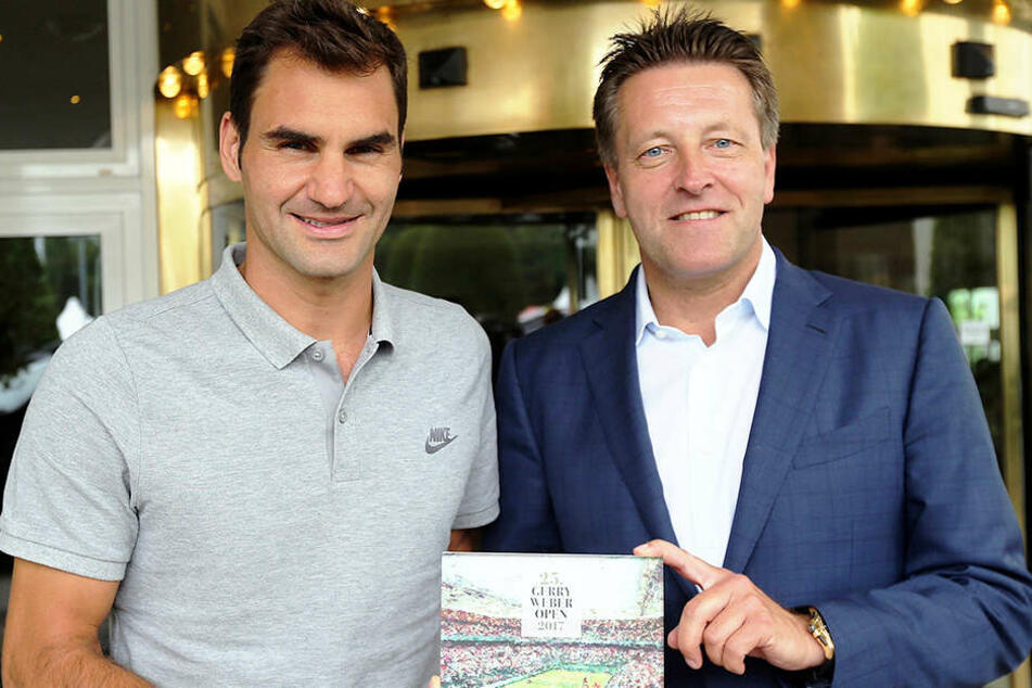 Ankunft von Tennis-Superstar Roger Federer (links) bei den GERRY WEBER OPEN! Zur Begrüßung überreichte Turnierdirektor Ralf Weber ein in Acryl eingefasstes Turnierplakat als Retromotiv.