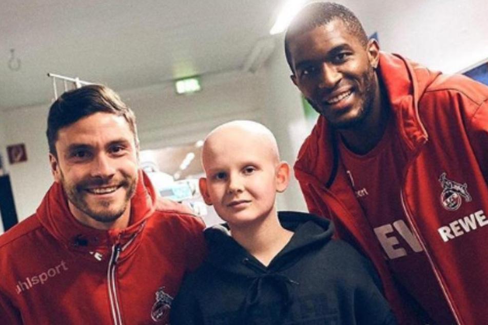 Jonas Hector (links) und Anthony Modeste (rechts) posieren mit einem kleinen FC-Fan.