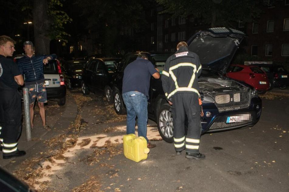 Einsatzkräfte begutachten den Motorraum des BMW.