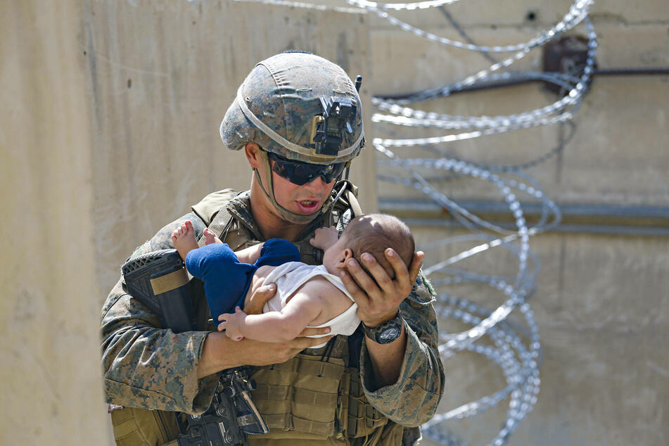 A US marine holding a baby as the evacuation operation continues.