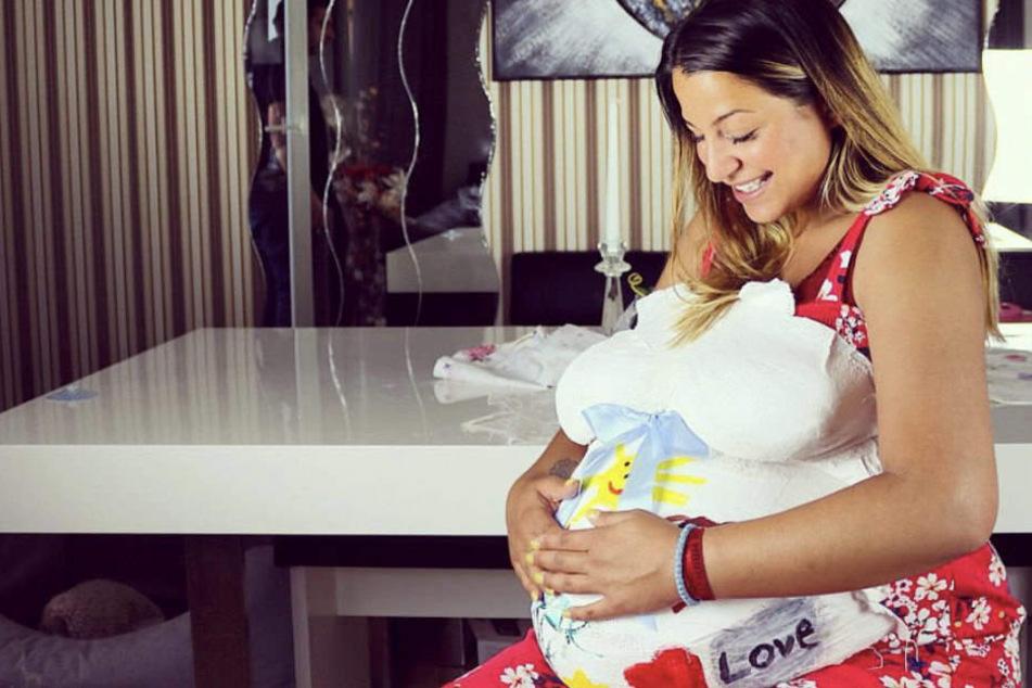 Jenefer verkündet auf dem Gipsabdruck ihres Babybauches den Namen des Kindes.