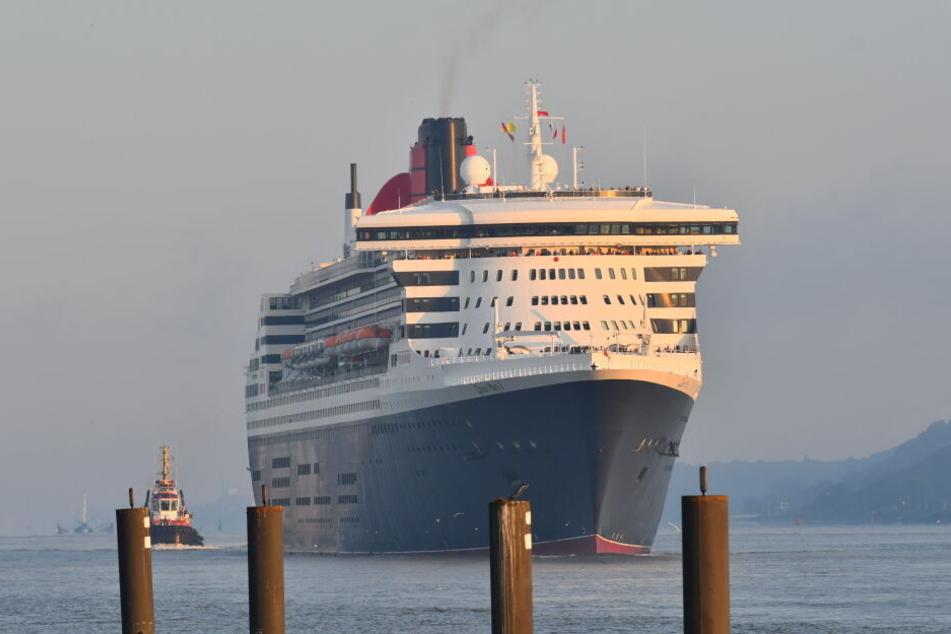 Die Queen Mary 2 gleitet im Morgengrauen die Elbe in Richtung Hamburg entlang.