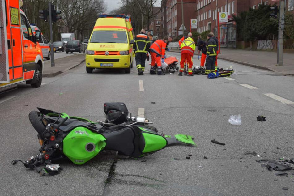 Das Motorrad ist nach dem Unfall deutlich beschädigt. Rettungskräfte transportieren eine Person ab.