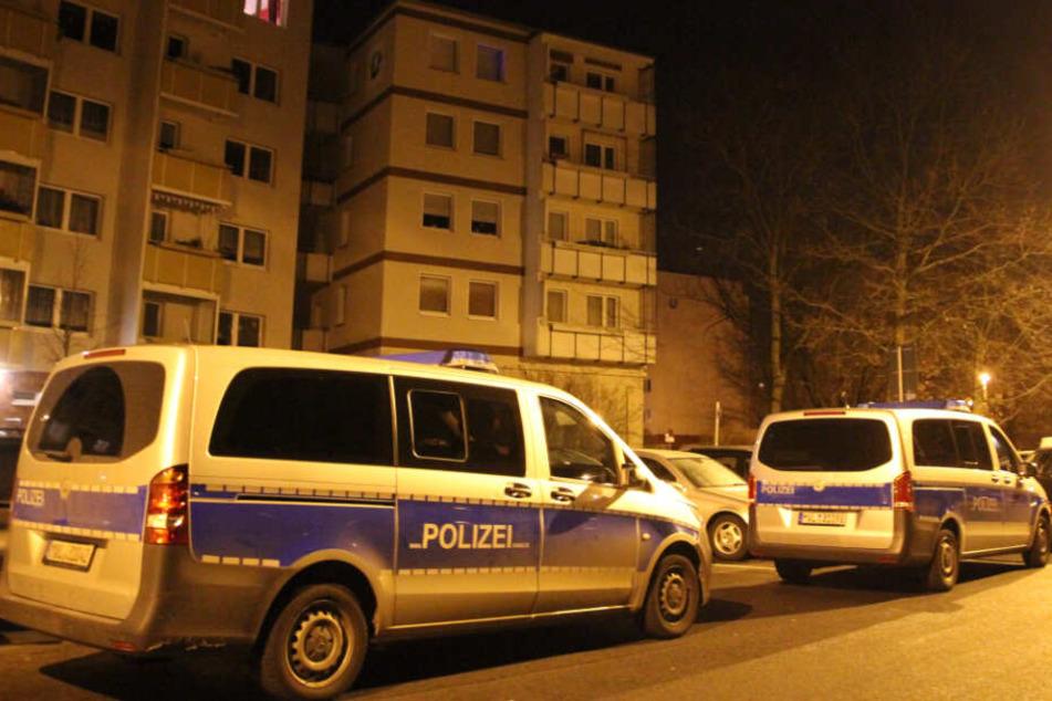 Vor dem Mehrfamilienhaus stehen zwei Polizeiwagen.