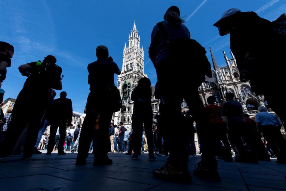 Touristen verfolgen das Glockenspiel auf dem Marienplatz in München. (Archivbild)