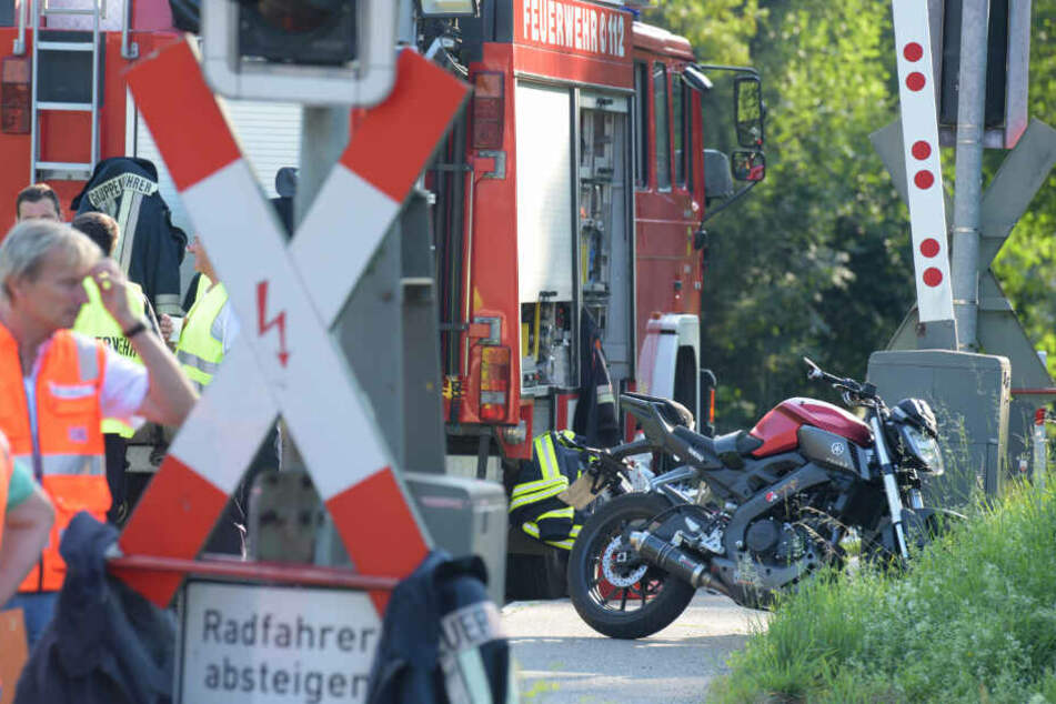 Ein verunglücktes Motorrad steht an einem Bahnübergang im bayerischen Harburg. Der Motorradfahrer wurde von einem Zug erfasst und tödlich verletzt.