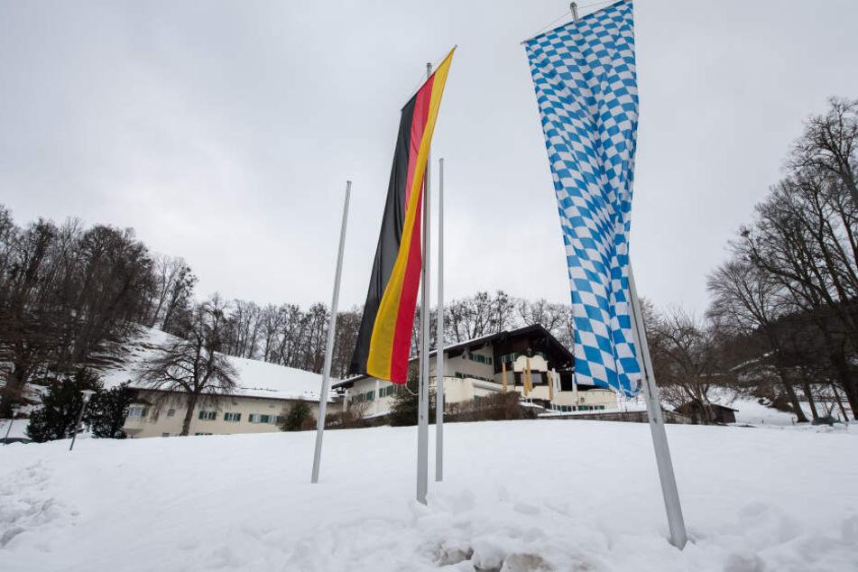Eine deutsche und eine bayerische Flagge wehen vor dem Tagungsort Sankt Quirin, in dem die Haushaltsklausur der bayerischen Staatsregierung stattfindet.