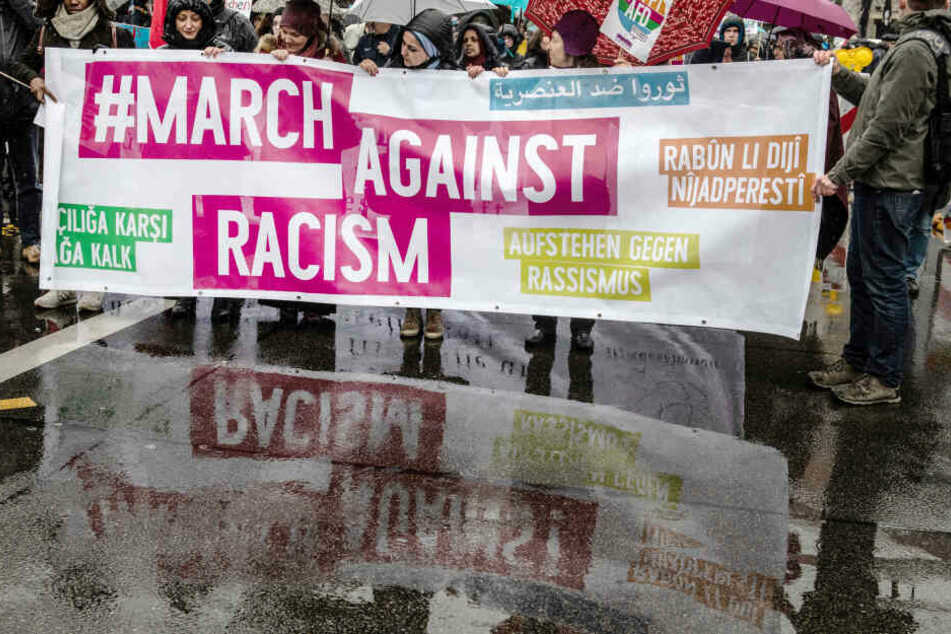 """Demonstranten stehen mit einem Transparent am Start der Demonstration """"Gemeinsam gegen Rassismus und Faschismus""""."""