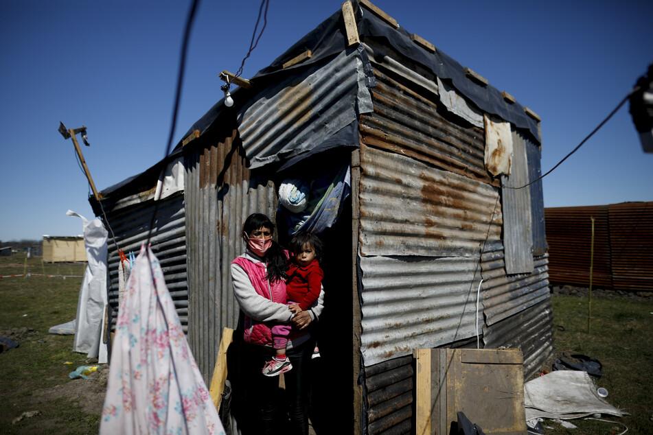 Argentinien, Guernica: Cecilia Avila hält ihre Tochter Triana, während sie vor ihrem behelfsmäßigen Zuhause in einem Camp steht.