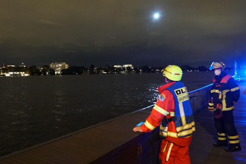 Einsatzkräfte stehen am Ufer, während ein Hubschrauber das Wasser absucht.