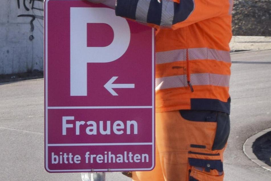 Ein Mitarbeiter der Stadt montiert an einem Parkplatz in Eichstätt ein pinkfarbenes Verkehrsschild.