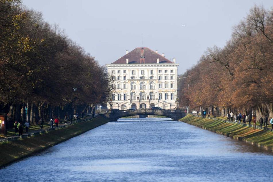 Spaziergänger spazieren auf den Wegen am Nymphenburger Kanal entlang. Im Hintergrund steht das Schloss Nymphenburg.