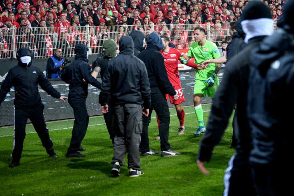 Unions Christopher Lenz und Unions Rafal Gikiewicz beruhigen vermummte Fans ihres Vereins nachdem die Hertha-Fans Pyrotechnik auf das Spielfeld schießen.
