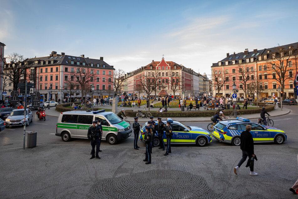 Polizisten stehen am Gärtnerplatz im Herzen der Stadt, während Passanten auf dem Platz verweilen.