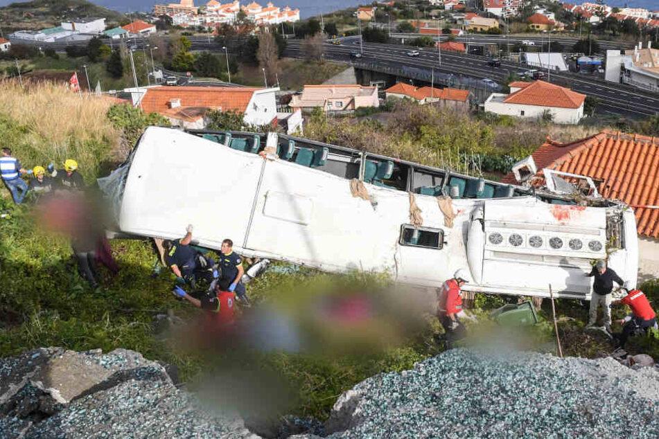 Rettungskräfte stehen nach dem schweren Busunglück auf der portugiesischen Ferieninsel an dem Bus.