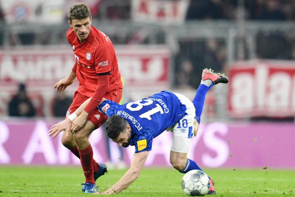 Thomas Müller (l.) von München schaut auf den strauchelnden Daniel Caligiuri von Schalke. Am 03.03.2020 trifft der FC Bayern im DFB-Pokal auf Schalke. (Archivbild)