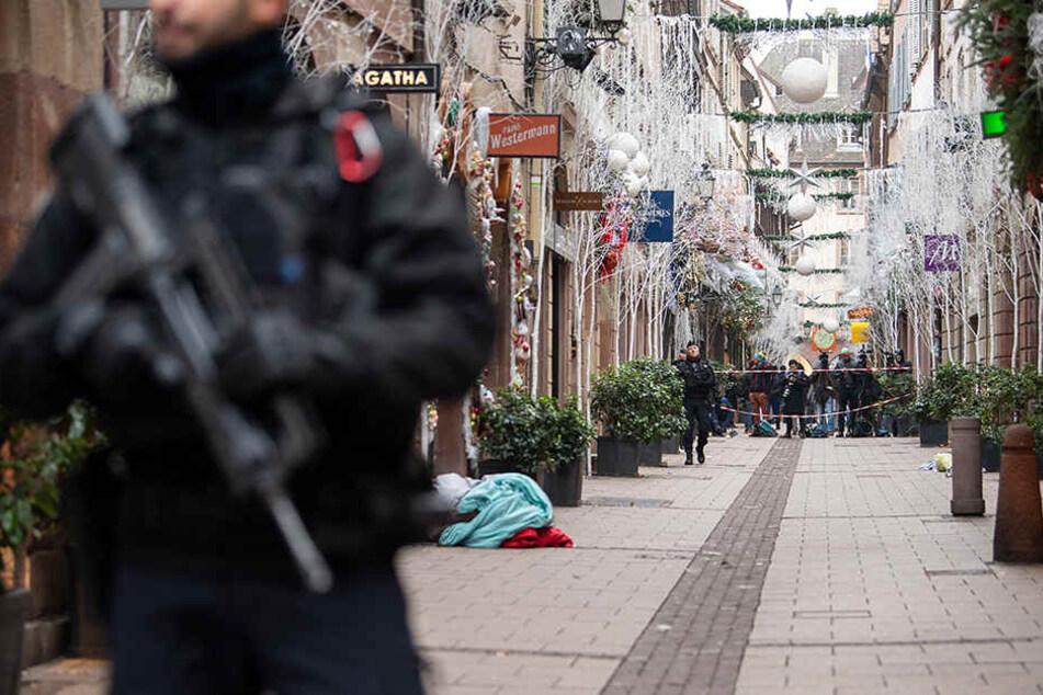 Ein Polizist steht nach dem Angriff in der Gegend des Straßburger Weihnachtsmarkts vor einem Tatort.