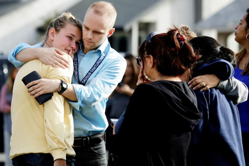 Ein Lehrer hält eine Schülerin tröstend im Arm.