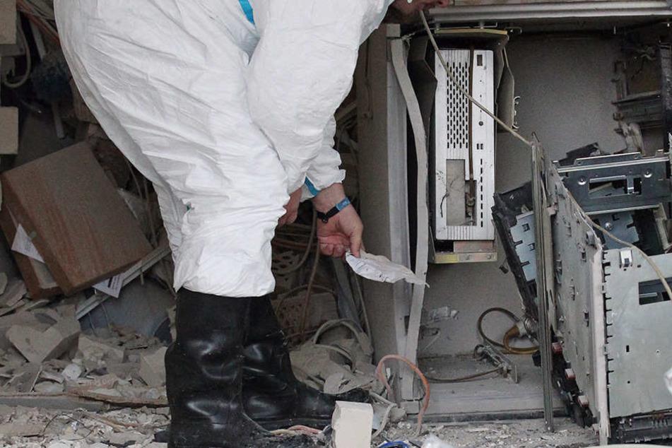 Ein Kriminaltechniker steht vor einem zerstörten Geldausgabeautomat. (Symbolbild)