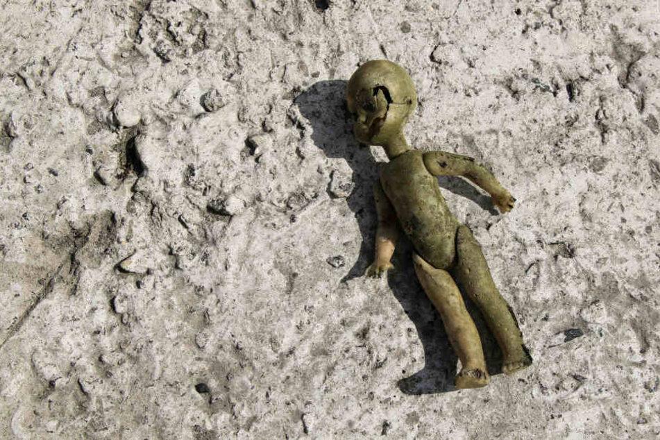 Eine kaputte Babypuppe liegt verlassen auf dem Boden (Symbolbild).