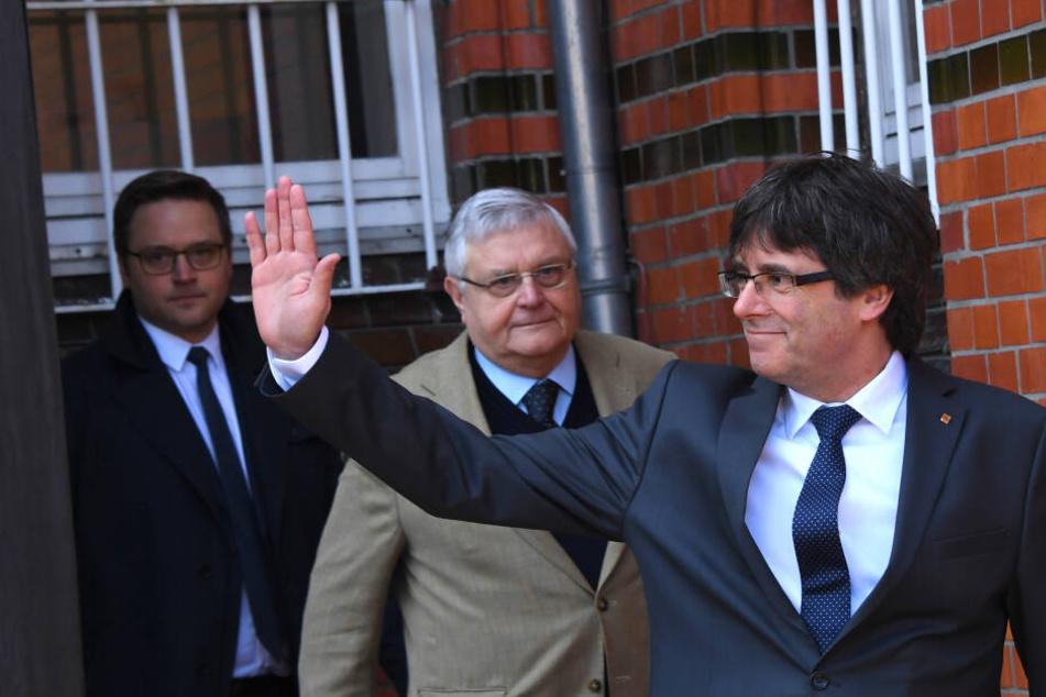 Carles Puigdemont, ehemaliger Präsident der spanischen Region Katalonien, als er mit seinen Anwälten aus der JVA Neumünster kommt und winkt.